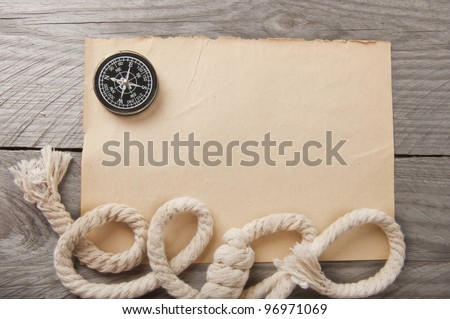 old compass and rope on the old paper against a dark background of the old tree - stock photo