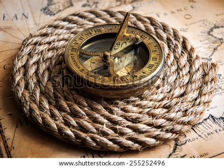 Old compass and rope on vintage map. Adventure stories background - stock photo