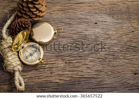 Old Compass and rope on wood background