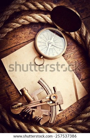 Old compass, astrolabe and rope on vintage paper. Adventure stories background. - stock photo