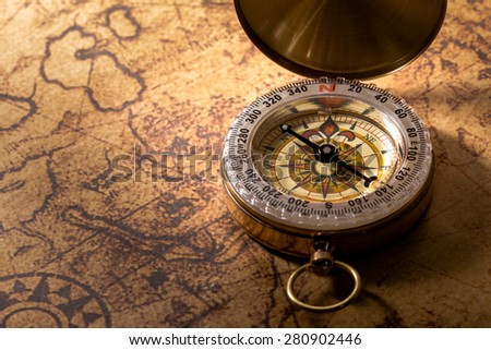 old compass on vintage map. - stock photo