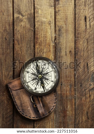 Old compass on wooden background with space for text - stock photo