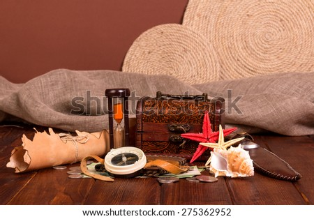 Old compass, treasure chest, knife, money and starfishes on wooden table - stock photo