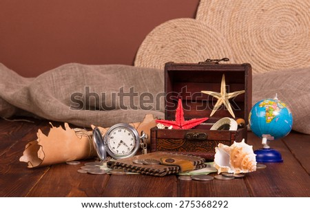 Old compass, treasure chest, knife, money, globe and starfishes on wooden table - stock photo