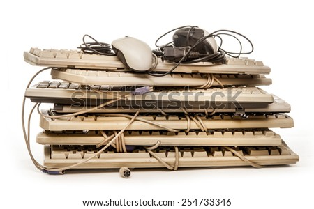 Old computer hardware and keyboards on white - stock photo