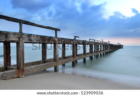 Old concrete bridge on the beach to the sea photo in sunset low lighting and dark shadow with long exposure shutter speed.