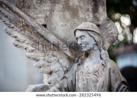 Old concrete statue of angel at Rasu cemetery in Vilnius Lithuania. Shot taken with a soft focus lens, shallow depth of field. - stock photo