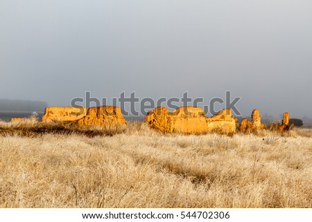 Old construction for livestock, meadow with frost and sky with fog.