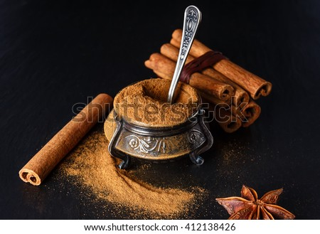 Old container for spices stuffed full of ground cinnamon. The photo in a dark key.