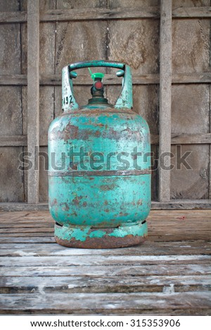 old cooking gas cylinder on old wooden background - stock photo