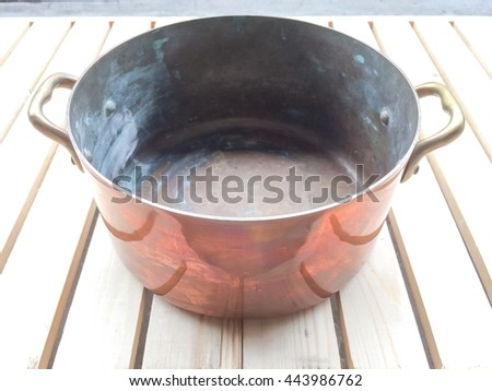 old copper pot on wood background - stock photo