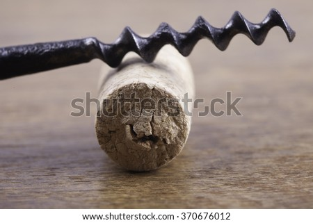 old corkscrew and wine cork on wooden surface macro closeup - stock photo