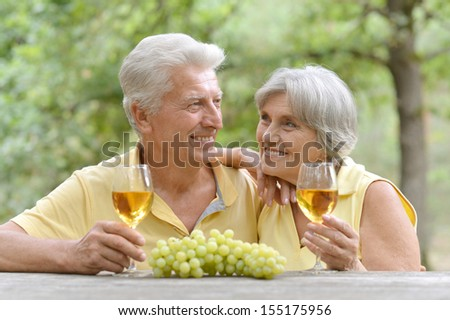 Old couple drinking wine and eating grapes at the table