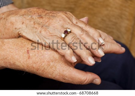 Old couple holding hands with ring on finger - stock photo