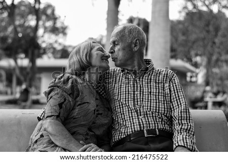 Old Couple in a Park About to Kiss - stock photo