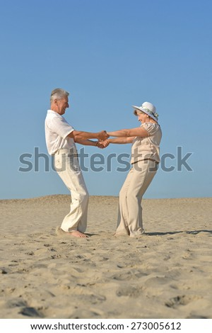 old couple in love walking barefoot in the sand - stock photo