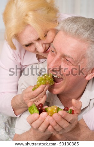 old couple lying on the bed and eats fruit