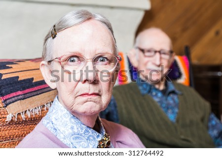 Old couple seating in livingroom woman scowling - stock photo