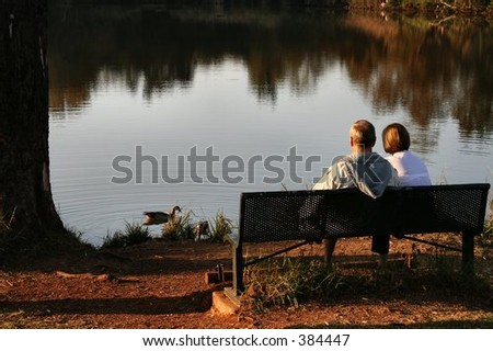 Old couple sitting at a lake feeding ducks in the afternoon. - stock photo