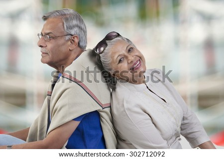 Old couple sitting back to back