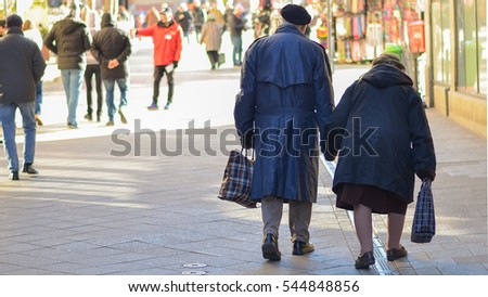 old couple walk on the street hand in hand with bags