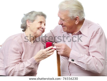 old couple with heart-shaped engagement ring on white background - stock photo