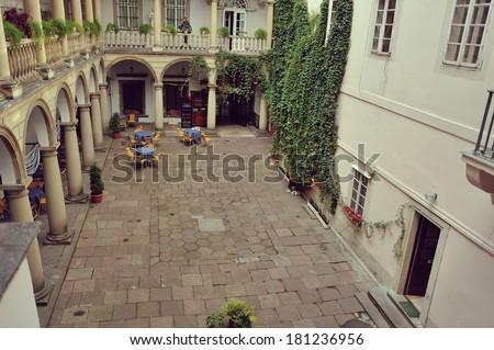 old courtyard with arches and white house with green ivy - stock photo