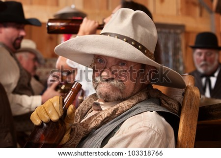 Old cowboy holding whiskey bottle in a saloon - stock photo