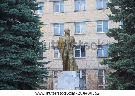 Old cracked golden Monument to Lenin in USSR between trees on retro house of white brick with many windows background