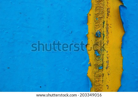 Old cracked paint pattern on concrete background. Peeling paint. Pattern of blue and yellow grunge material. Damaged paint. Scratched old plate - stock photo