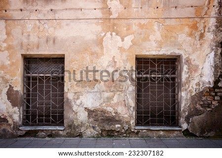 Old cracked street wall with some windows - stock photo