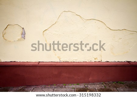 Old cracked wall  fresh painted in yellow and pavement  - stock photo