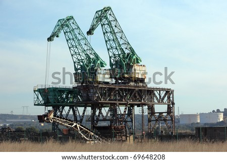 Old cranes in a dock of a scrapyard