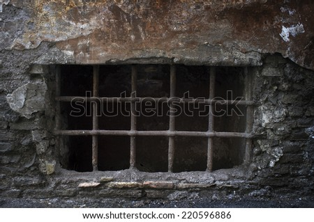 Old creepy cellar window with bars. - stock photo