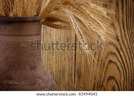 Old crock with a bunch of wheat ears (against the background of a wooden wall, with focus on wheat ears), retro style - stock photo