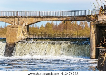 Old crumbling water gate of the abandoned hydroelectric power station - stock photo