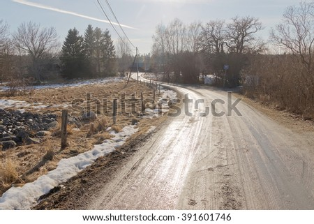Old curved country road in the swedish countryside a sunny day during spring time - stock photo