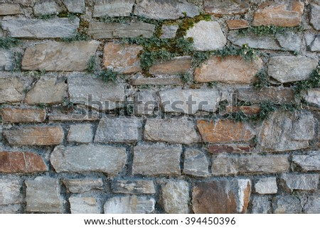 Old cut stone wall background texture with uneven rectangular blocks in rows with a rough weathered surface, full frame view