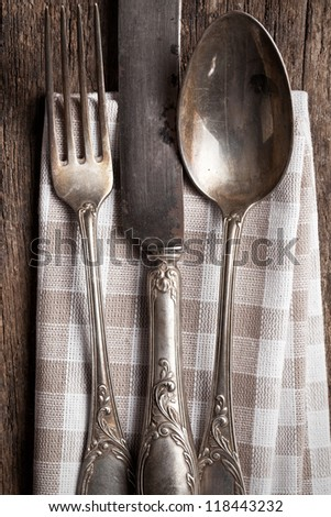 old cutlery on wooden table - stock photo