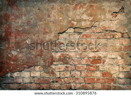 Old damaged brick wall with plaster - stock photo