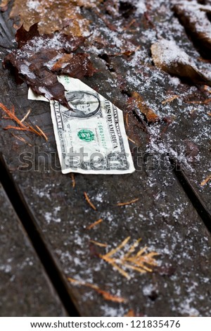 old damaged dollar bill left behind in a cold winter background - stock photo