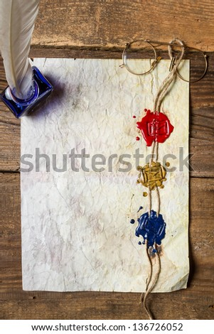 Old damaged sheet of paper with inkwells and three sealing wax - stock photo