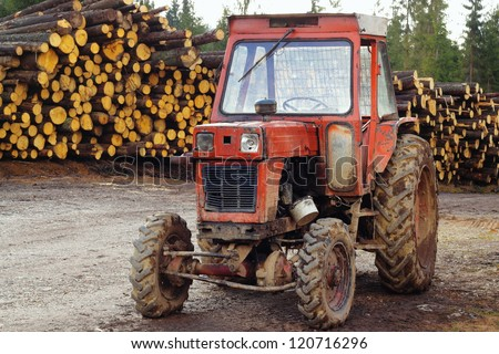 old damaged tractor on a mountain road and a stack of felled trees in the background - stock photo