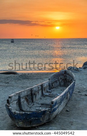Old damaged wooden canoe with a beautiful orange sunset in the background in Santa Marta, Colombia