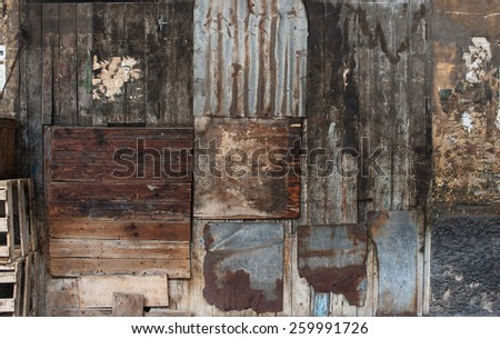 Old dark brown wooden and tin vintage wall or fence background - stock photo