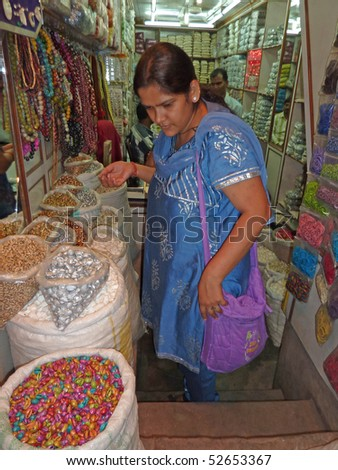 OLD DELHI, INDIA - NOV 3 : Indian woman in colorful saris browses the souvenir shops in the markets near Chandri Chowk on Nov 3, 2009, in Delhi, India. - stock photo