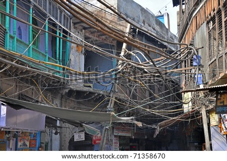 OLD DELHI, INDIA - 24 OCTOBER: Picture of Indian chaotic electrical wiring in Old Delhi on October 24, 2009. Unsatisfying conditions of wiring cause power problems in Delhi. - stock photo