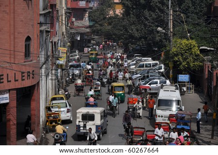 OLD DELHI, INDIA -OCTOBER 24: Traffic jam with rickshaws, motorbikes, cars and pedestrians on local city street on October 24, 2009 in Old Delhi. Traffic jam is the main problem of transportation in Delhi. - stock photo