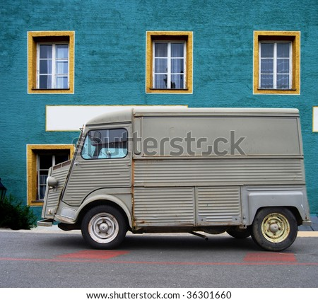 Old delivery van in front of a colorful house - stock photo