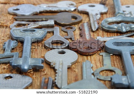 Old different keys on wooden board - stock photo